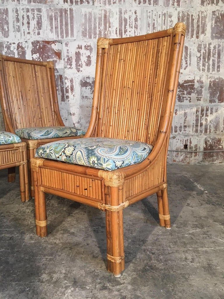 Set of 4 high back split pencil reed rattan dining chairs add a tropical touch to any decor. Excellent vintage condition with minor signs of age appropriate wear. Structurally sound.  Professional reupholstery available, ask for details.