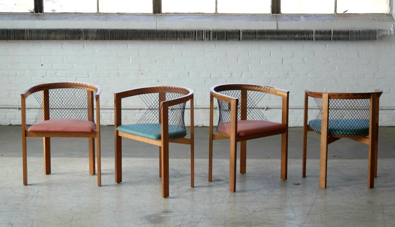 Set of four stunning sculptural string chairs designed by Niels Jørgen Haugesen for Tranekær Furniture Denmark, circa 1980. Each chair features angular wood frames in satin-finished cherrywood. The minimal, post modernist style frame is complemented