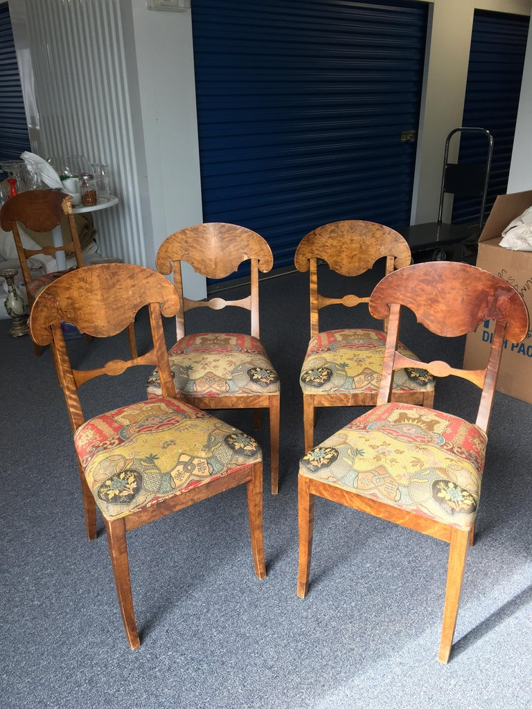 Set of four Swedish Biedermeier side chairs with silk fabric. The silk fabric is in very good condition. Two chair backs have had considerable visible repairs. All chairs are structurally sound. Some chipping to veneer.