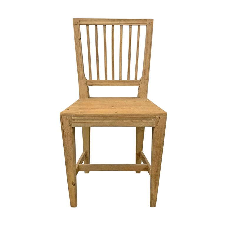 A charming set of four early 19th century Swedish Gustavian period pine dining chairs with simple square back and square tapered legs all held together with pegged construction. Traces of the original white paint remain.
