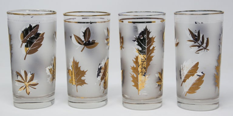Set of four vintage cocktail glasses. Manufactured by Libbey, 1950s Hollywood Regency. Decorated with a classical gold leaf pattern on frosted glass. In good condition, perfect for the holidays and gorgeous on display in a cabinet or bar while