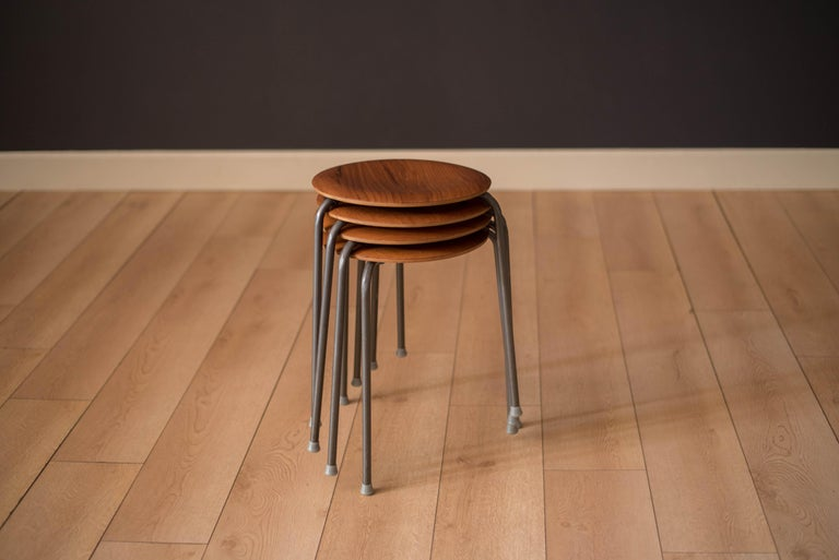 Mid century set of stools or end tables made in Denmark circa 1960s. This stackable collection features a curved teak tabletop and a three legged base. Price is for the set of four.   Top 13