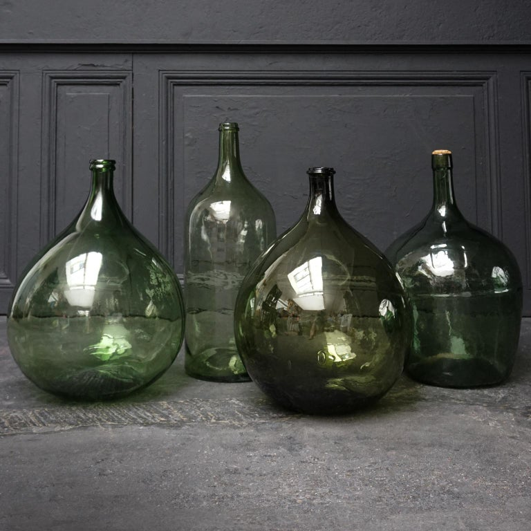 Very decorative set of 4 old green blown and pressed glass bottles also know as Demijohn, Lady Jeanne, Dame Jeanne or Carboy. Made and used somewhere between early 20th century and 1960s.   The two bulbous ones of them have a capacity of 25