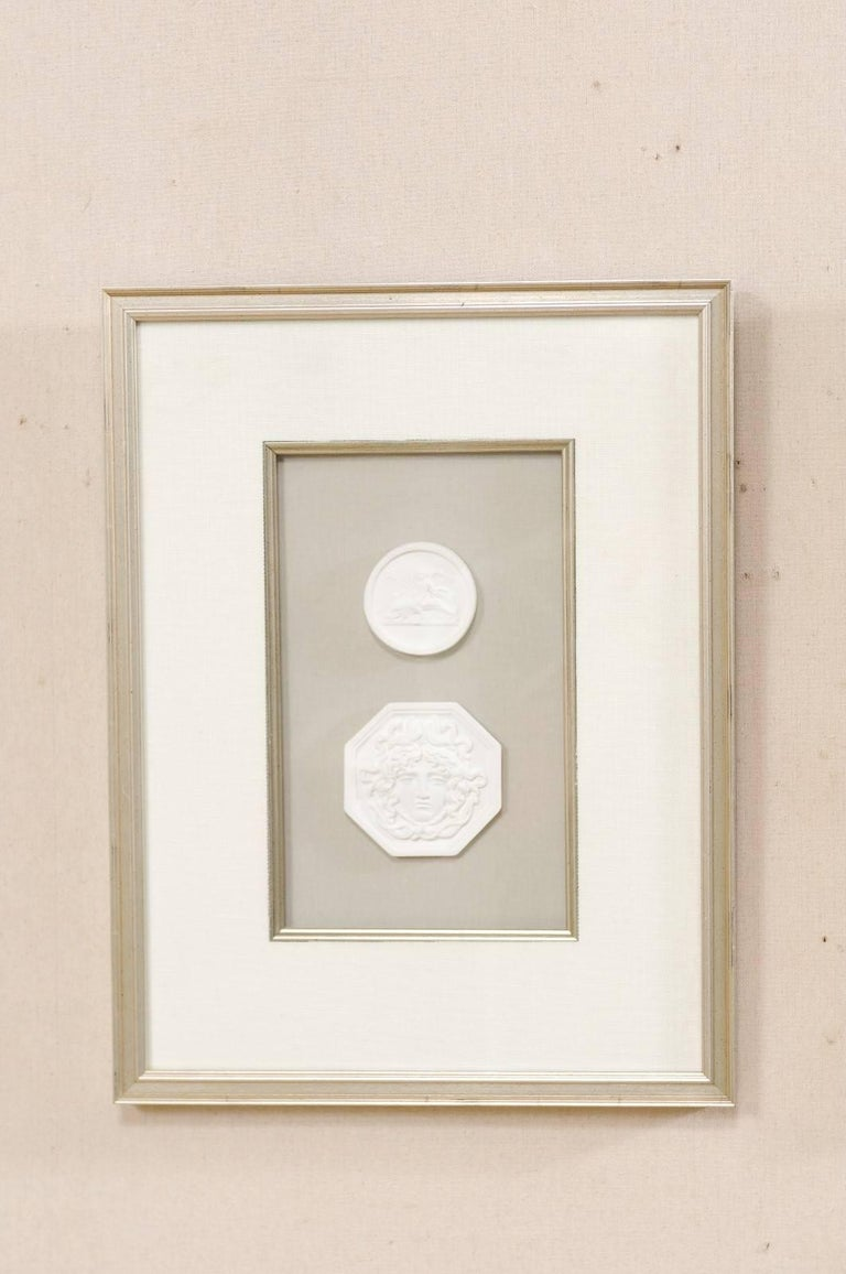 A collection of four framed assortment of white Italian intaglios. This is a set of hand-cast intaglios (from the original antique Italian Intaglios) which have been mounted and set within custom silver leafed frames. The details of these