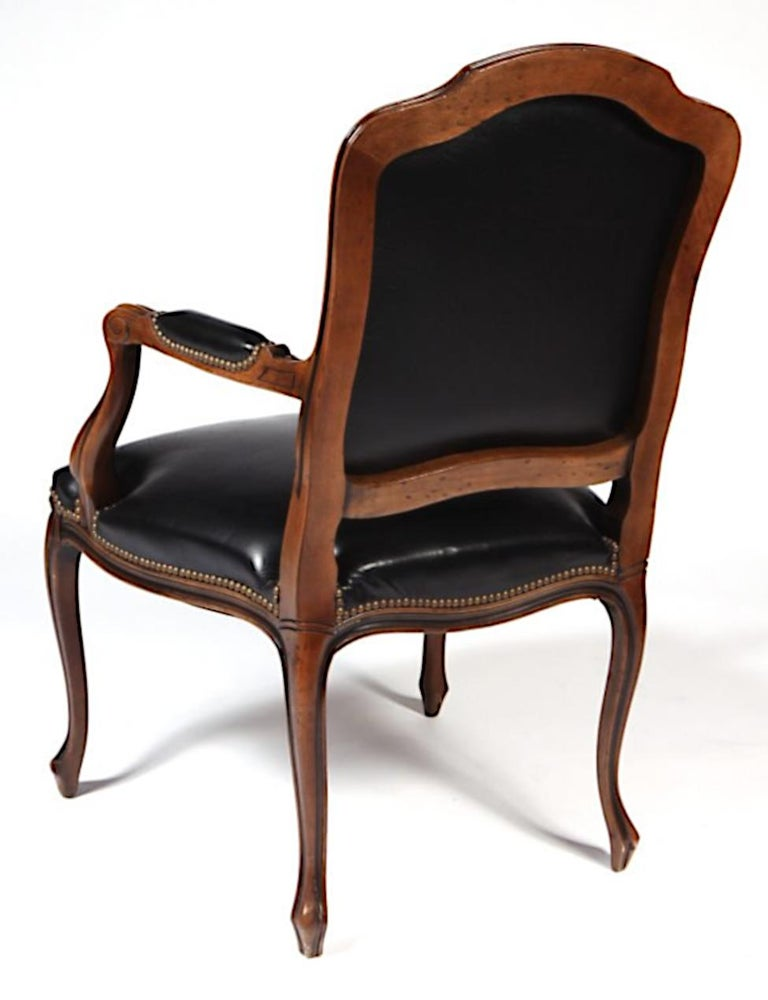 Set of four vintage Italian carved walnut French country or Louis XV style armchairs. Chairs feature black colored leather upholstery, finely carved solid wood frames, upholstered armrests, nailhead trim and cabriole legs. Great quality Italian