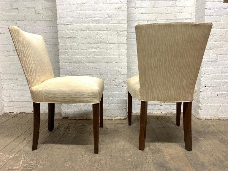 Set of four walnut upholstered dining chairs. The chairs have solid walnut legs and the original upholstery.