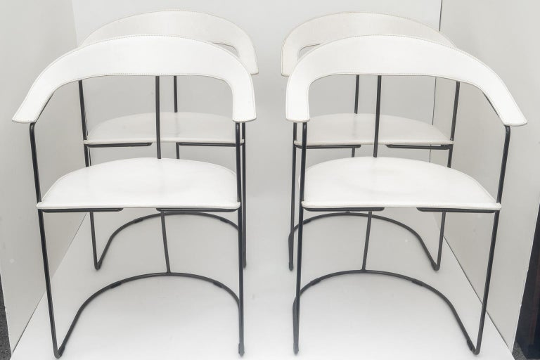 These four slope-backed armchairs in white leather were created by Arrben in the 1980s-1990s. The chairs are very simple in design and have a great sculptural presence.   Note: The tubular frames are solid and in a polished gun-metal finish.