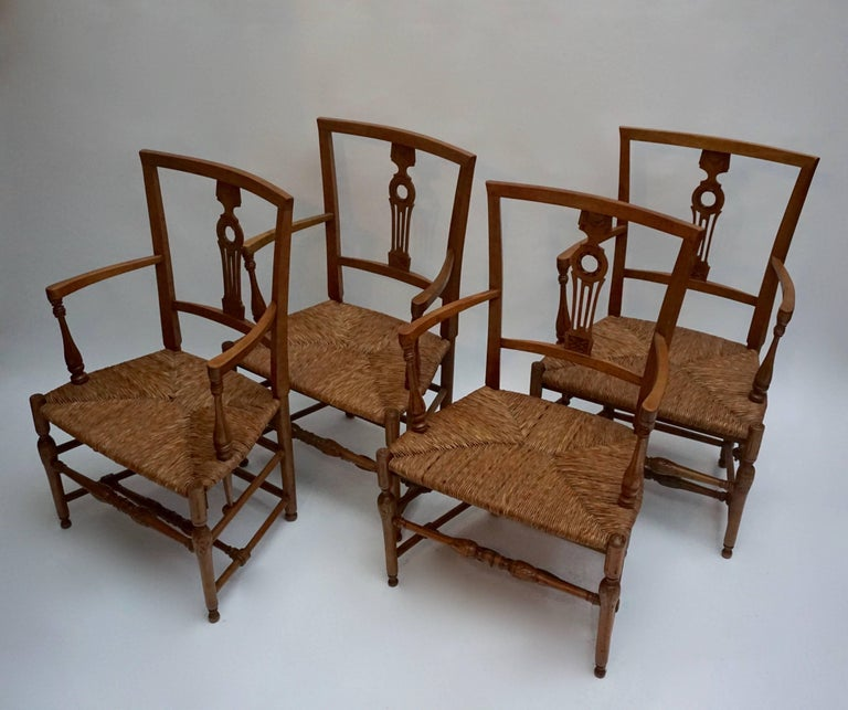 Interesting set of four armchairs with solid wooden frame and wicker seats.