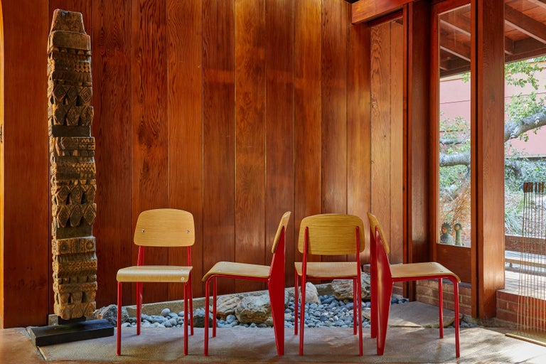 Set of four wood and metal chairs in the style of Jean Prouvé. Executed in wood and red painted metal. A high quality chair, date and manufacturer unknown.  Price is for the set.