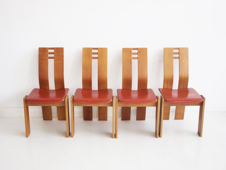 Set of four chairs with maple wood frame and brick color leather seat covers, in the style of Pierre Cardin. Manufactured in Italy in the 1950s.