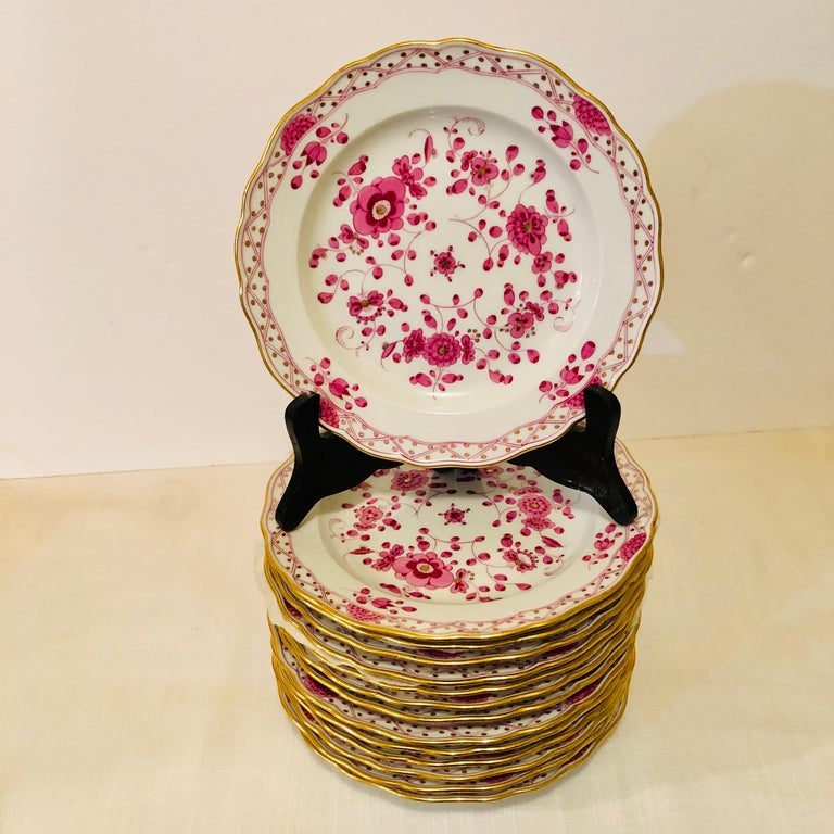 This is an exquisite set of fourteen Meissen purple Indian pattern dessert plates from the 1890s. It has detailed paintings of pink flowers with some purple and gold accents on a white ground. The detail of the painting on these dessert plates is