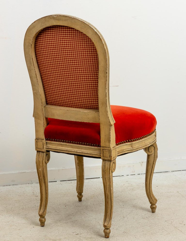 Set of fourteen French dining chairs upholstered in orange velvet with distressed finish, circa 1920s. The chairs also feature metal nail head trim and scrolled legs. Please note of wear consistent with age including finish loss and paint loss. One