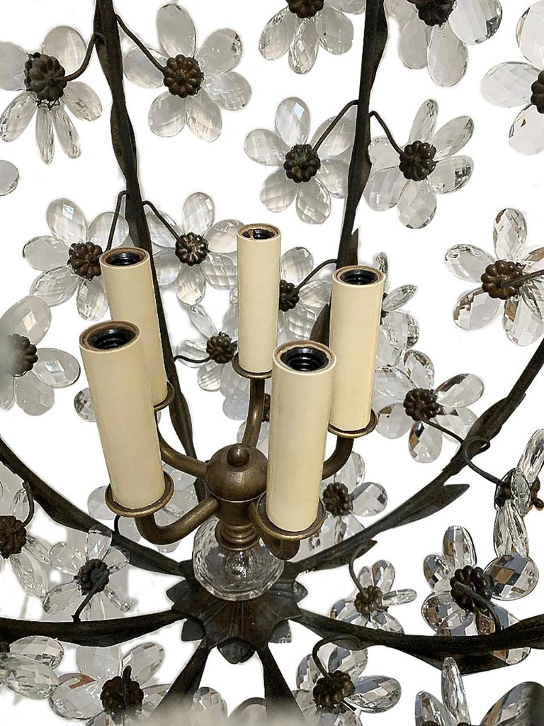 A set of three French circa 1930s patinated bronze and crystal flowers chandeliers with a 5-light interior cluster. Sold individually.