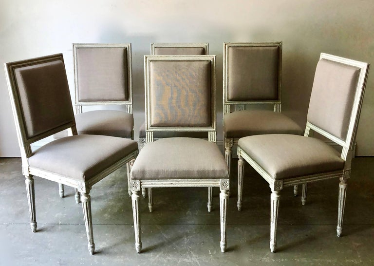 Set of six French Louis XVI style chairs with wood frames in lovely cream-grey-blue painted finish in richly carved frame, fluted leg and cubic blocks decorated with florets. Upholstered in linen and finished with the Classic decorative cimp,