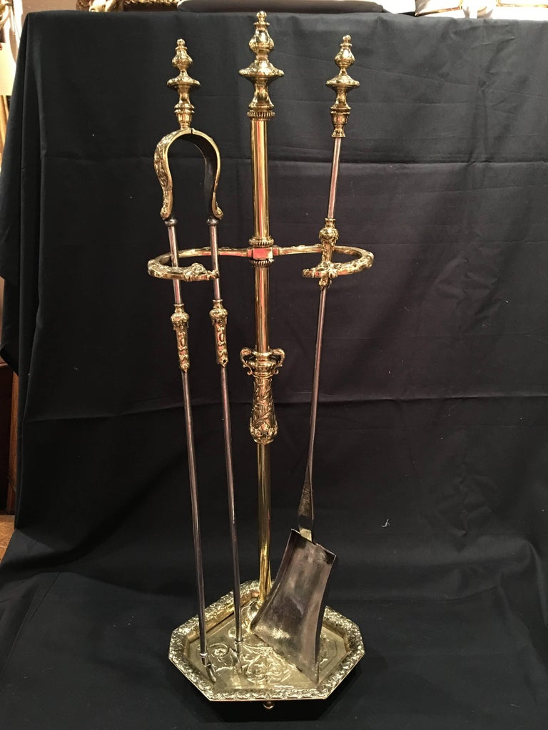 Set of French polished brass fire tools on a decorative stand, 19th century.