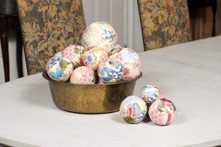 A set of unique French vintage cloth balls from the 20th century displayed in an antique circular brass bowl. Created in France during the 20th century, this set of cloth balls charms us with its colorful décor and variety of sizes. Ranging from 3