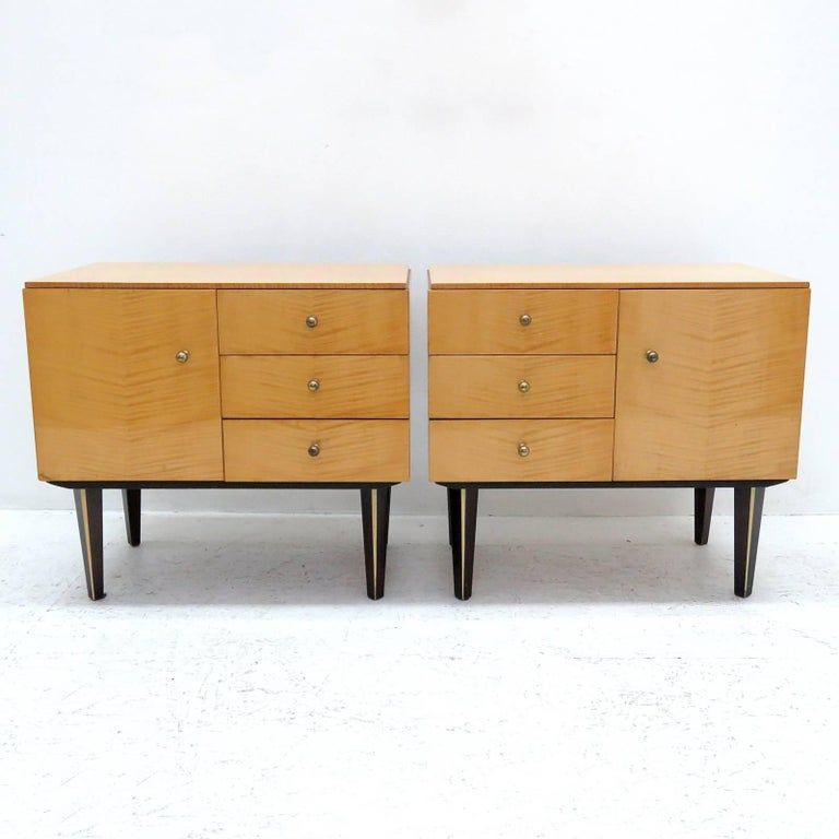 wonderful set of 1950s German birch veneer nightstands with one door and three drawers each, brass hardware, legs painted black with a decorative egg shell colored vertical strip.