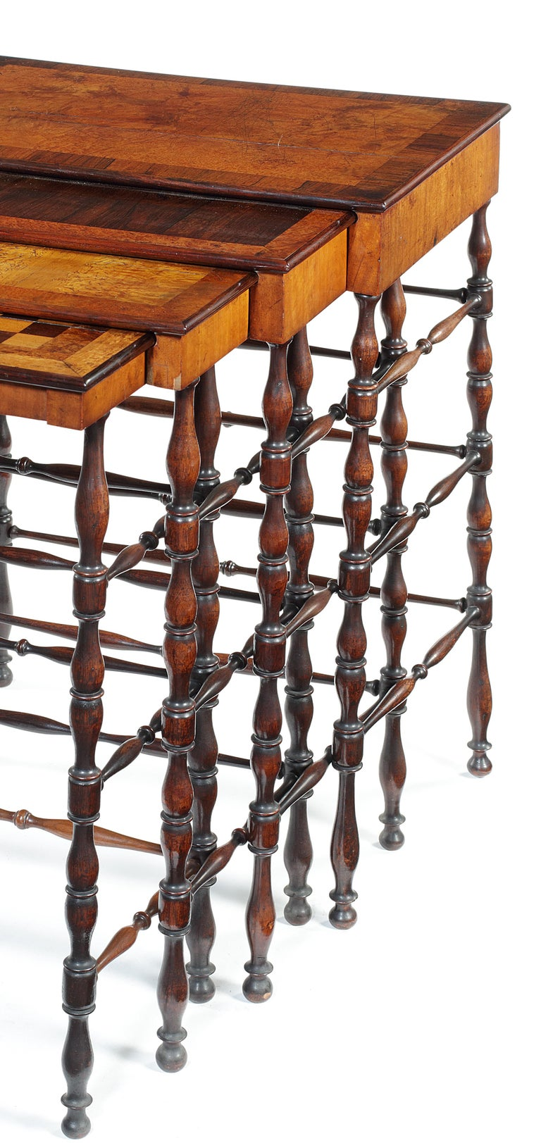 A set of Regency amboyna, thuya, maple and rosewood banded quartetto tables attributed to Gillows with rectangular tops, the smallest with chequerboard, on baluster turned legs joined by stretchers, the largest 58cm wide, 41cm deep, 74cm high (4).