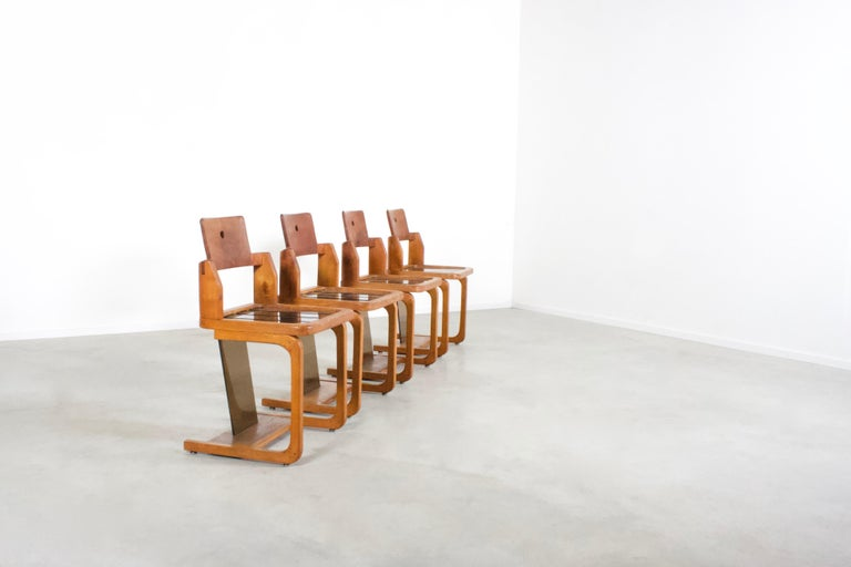 Rare set of four French chairs in very good condition.  Made in France in the 1960s   These chairs exude a rustic yet modern vibe. Perfect for any Mid-Century Modern, contemporary or Minimalist abode.  A combination of a solid teak frame with smoked