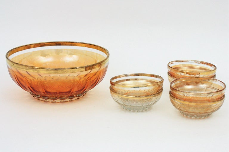 Beautiful set of Iridiscent amber and clear pressed pattern glass gold rim bowls. Spain, 1960-1970. Six small bowls and a large centerpiece bowl. The whole set has a pressed ball and rib pattern; a ribbed pattern surrounding the bowls and a ball