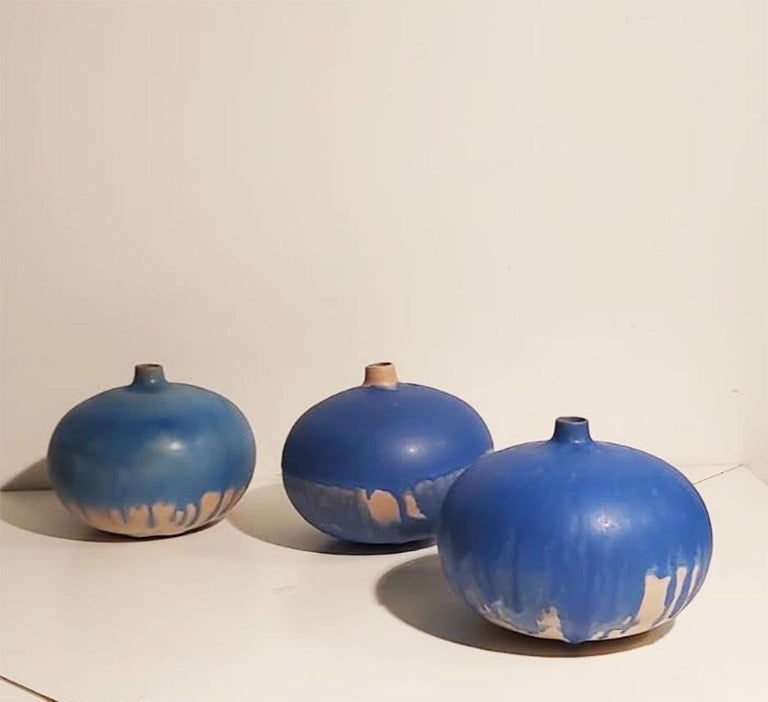 Set of three vases with three different blue nuances,  with shape of flattened sphere and small elegant top opening. Signed under the base  Measure: diameter 19 cm.