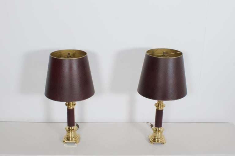 High quality neoclassical table lamps in very good condition.  Manufactured by Maison Jansen, France, 1970s  Heavy solid brass wrapped in a burgundy natural leather  The shades are also made in burgundy leather and they are gold on the