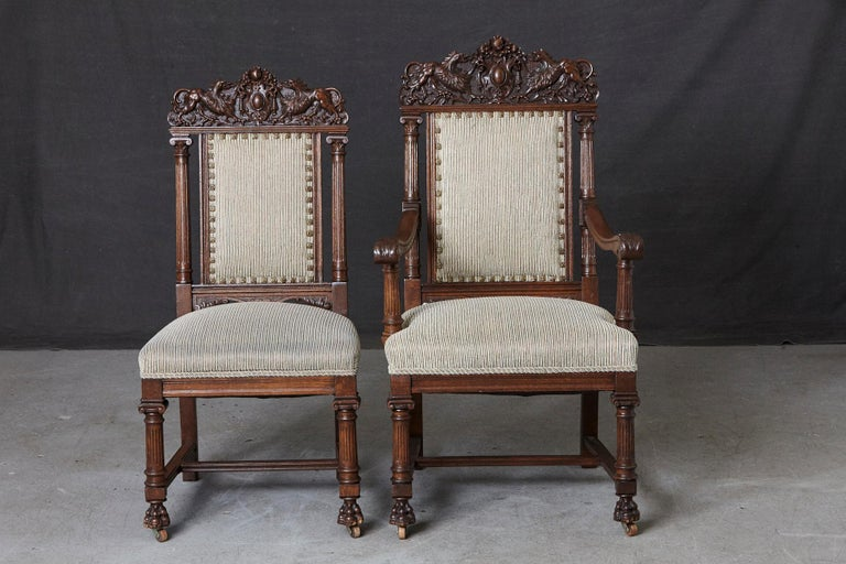 Pair of late 19th century Renaissance style 'his and her' or king and queen style throne chairs. Solid oakwood frames with intricate carvings to the top and along the frames and legs, mounted on claw feed.