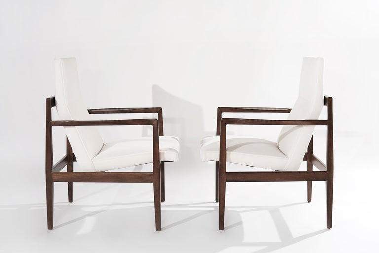 Pair of high-back lounge chairs designed by Jens Risom, featuring fully restored open-arm walnut frames, boasting clean, elegant lines from all angles. Newly upholstered in mohair by Holly Hunt.   Other designers from this period include Finn Juhl,