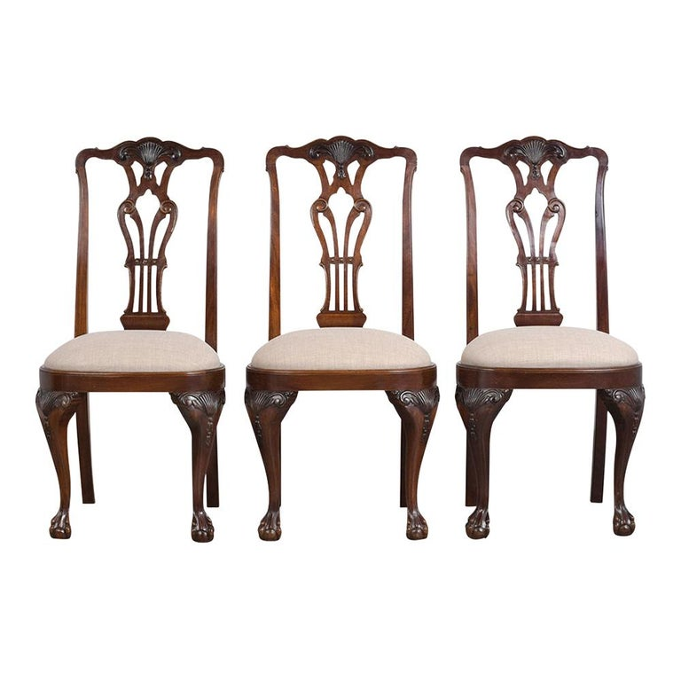 This Set of Six Late 19th Century Regency Style Dining Chairs are made out of mahogany wood with a rich mahogany color stain and a new semi-gloss finish. These antique chairs feature hand-carved details of scrolls & leaves, seats have been