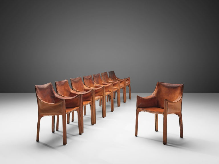 Mario Bellini for Cassina, set of eight cab 413 armchairs, Italy, 1979.  Conceptually, the chair was designed to become marked and shaped over time by its user. The leather skin fits like a glove over the steel skeleton and fastens with four zips.