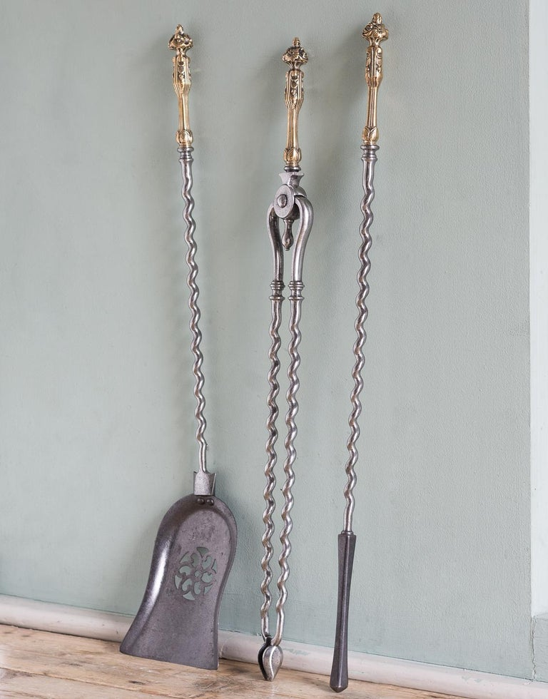 A set of mid-19th century brass and steel fire irons, comprising tongs, shovel and poker, with wrythen stems.