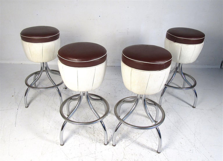 This stunning set of four vintage modern bar stools feature a backless seat and a chrome base with a footrest. The two-tone vinyl is sure to complement any setting. Please confirm the item location (NY or NJ).