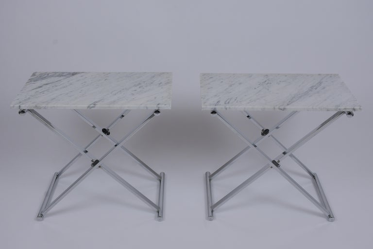 These pair of Mid-Century Modern end tables are made out of steel and marble, these sides tables feature new white Carrara marble top with flat polished edges resting on a chrome X-shaped design pedestal bases newly polished. These Sleek design