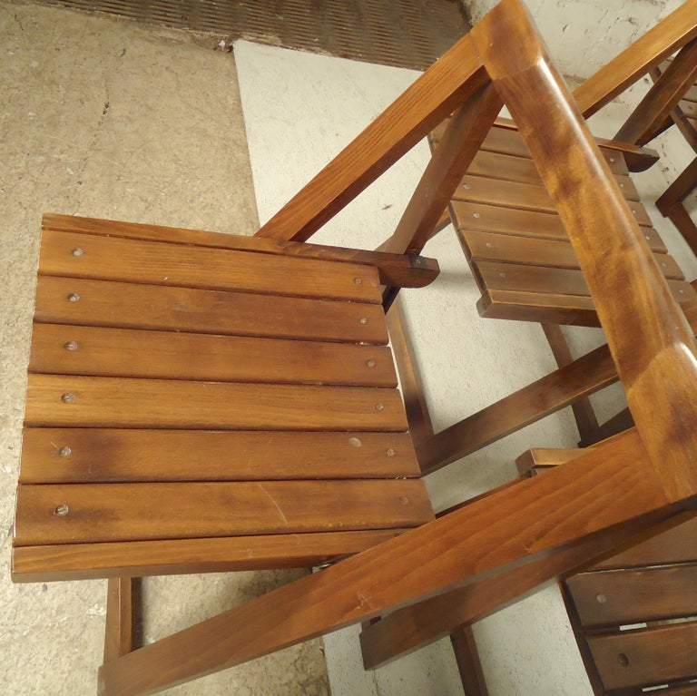 Vintage modern folding chairs with slat seats and curved backs. (Please confirm item location - NY or NJ - with dealer).
