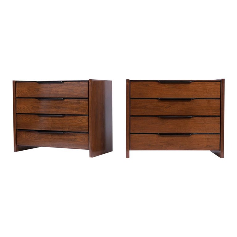 This Pair of Mid Century Walnut Chest of Drawers has been professionally restored and features a sleek design newly stained in a black and walnut color combination with a lacquered finish. The nightstands come with four large drawers, each with a