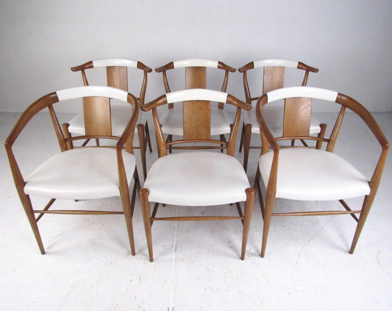 This stylish set of six vintage modern dining chairs by Heritage-Henredon of North Carolina feature solid walnut construction with upholstered leather seats. Mid-Century Modern design, sculptural seat backs, and quality American construction adds to