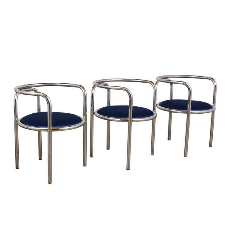 This Vintage Set of Six Mid-Century Modern Chrome Dining Chairs have been fully restored, and feature a barrel back chrome frame in very good condition. The armchairs have also been newly upholstered with blue velvet fabric. These Sleek 1970's