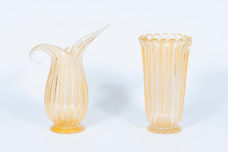 Set of Murano glass ribbed vase and pitcher with 24-karat gold, in style of Barovier, Italy, 1980s. The masterpieces come in different shapes: one has an oval base and an undulated edge on top, while the other is a pitcher with a stylized handle