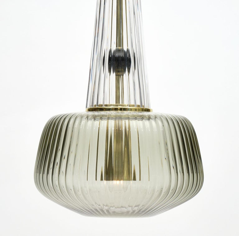 Set of Murano glass ridged pendants in the style of Ettore Sottsass. We have two sets of these beautiful fixtures available and each includes a green fixture, a smoke fixture, and a pink fixture. They have been newly wired to fit US standards. The