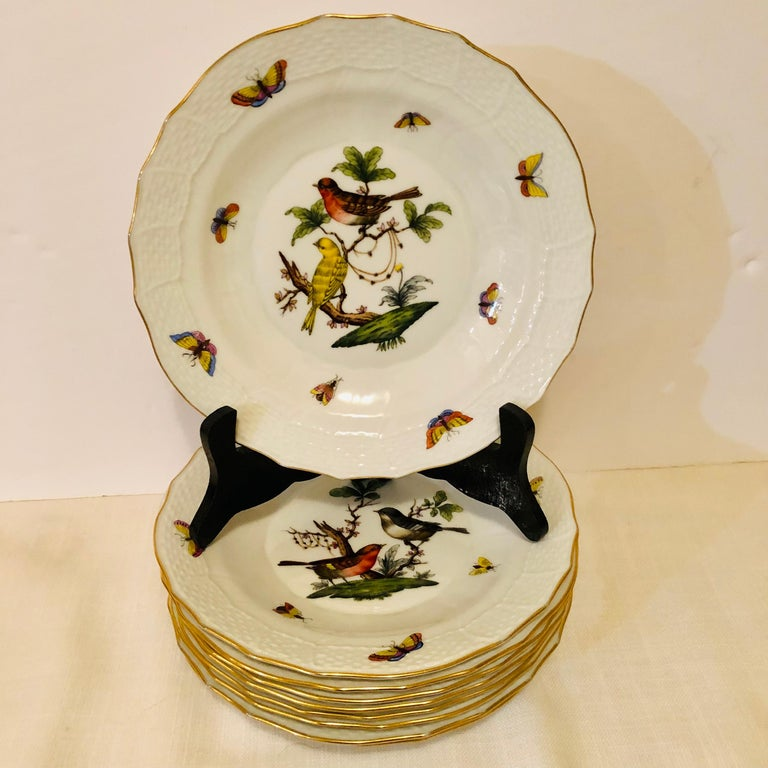 This is a lovely set of nine Herend Rothschild Bird dessert plates, each painted with two birds and decorated with accents of butterflies and flowers on a white ground. These would make a lovely naturalistic addition to any dessert service. The