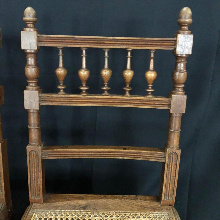 Beautiful and immaculate set of nine dining chairs from Normandy, France! These oak Henri II chairs have caned seats, all in great condition. The carving on each chair is detailed, with the ladderback accentuated with stunning carved spindles,