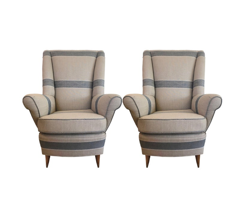 Striped upholstered Mid-Century Modern 1940s armchairs with out-curved armrests, tall backrests and medium stained, tapered wood legs. Chairs can be sold in pairs.  In the style of Paolo Buffa.