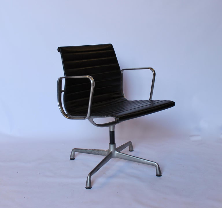 A set of office chairs from the series Aluminum Group Vitra, model EA 107, designed by Charles and Ray Eames in 1958. The chairs are with black leather and frame of aluminium, from the 1970s.