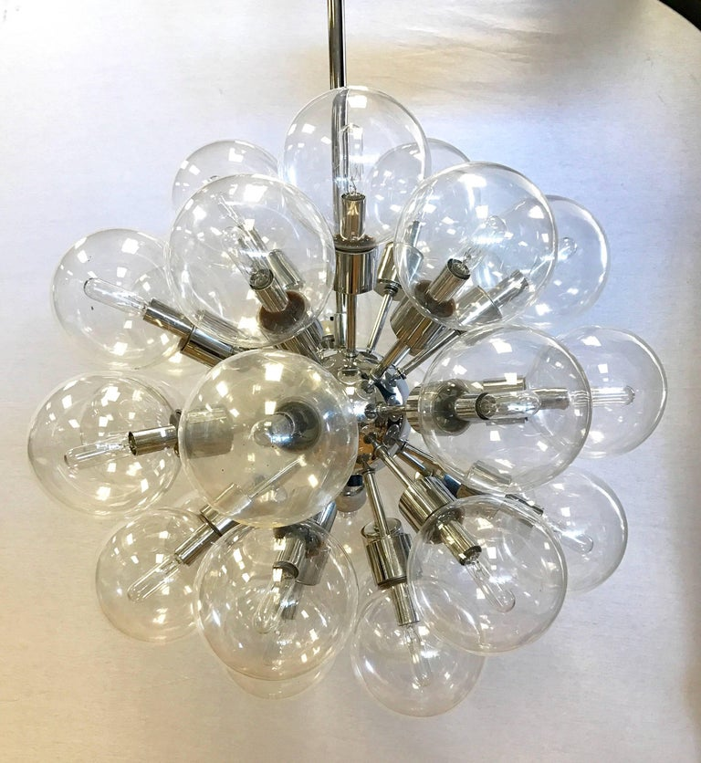 Coveted pair of matching Mid-Century Modern Lightolier 30-light sputnik chandeliers, circa 1960s. Each features thirty original glass globes on polished chrome spokes radiating from a central chrome nucleus. They are made of polished chrome and have