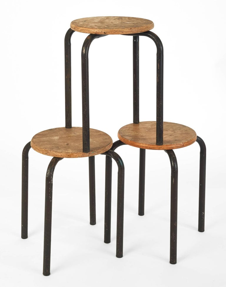 Whimsical set of three stackable painter stools in the style of Jean Prouvé, their utilitarian laminated wood seats and lacquered metal bases a model of functional design.