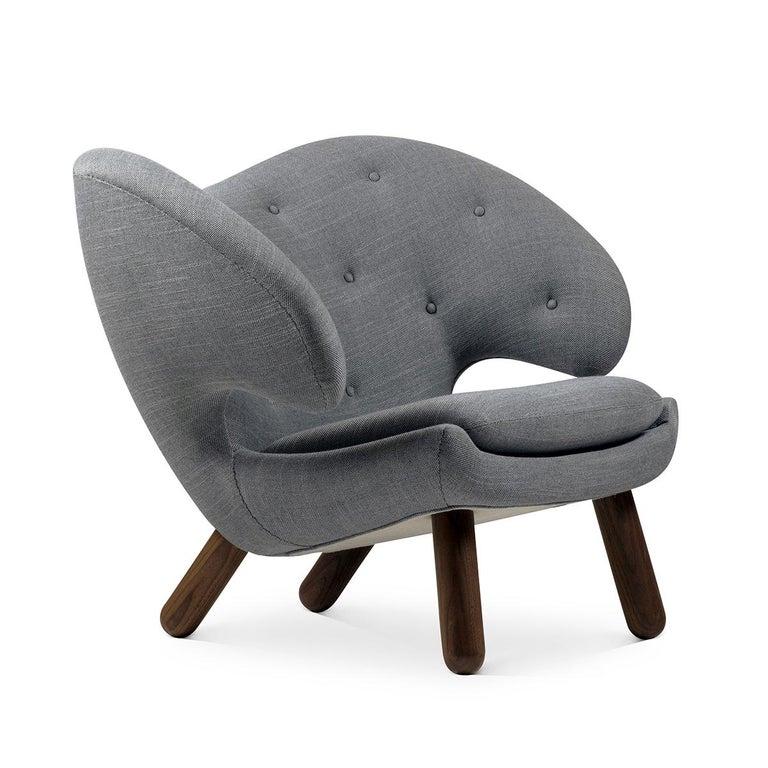 Pelican chair designed by Finn Juhl in 1940, relaunched in 2001. Pelican table designed by Finn Juhl in 1940, relaunched in 2014. Manufactured by House of Finn Juhl in Denmark.  About Pelican Chair: Pelican chair was probably the one furthest