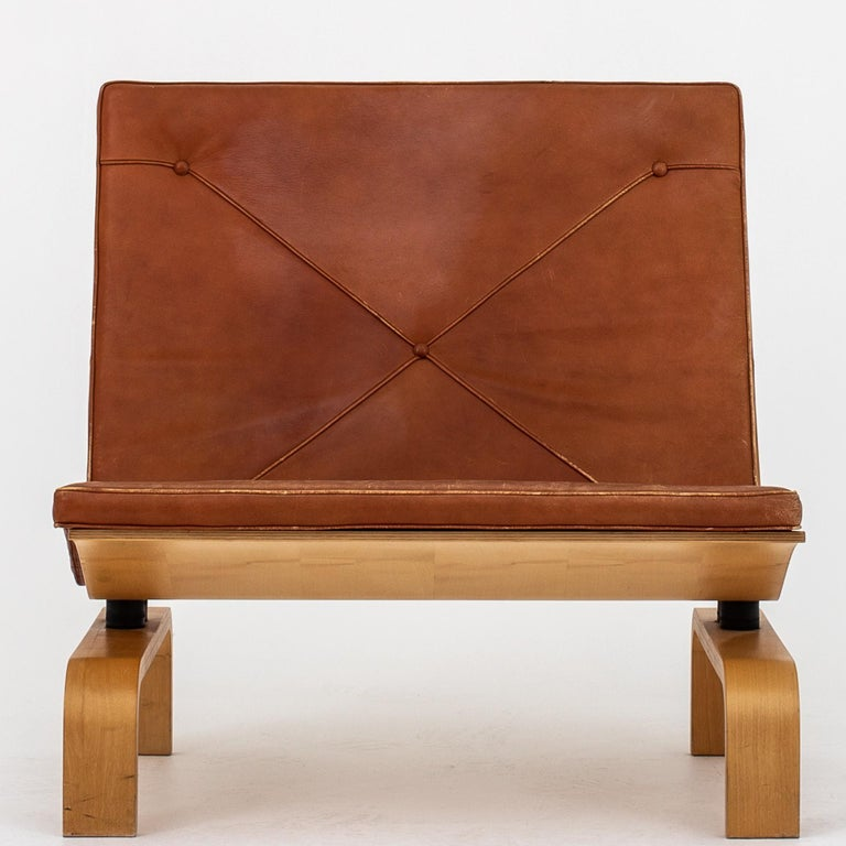 PK 27 - Set of 2 easy chairs and 1 coffee table w. special measurements. The set is made in maple and w. original, patinated cognac leather. Designed in 1971. Table 60 x 60 Height 25 cm. Maker E. Kold Christensen.
