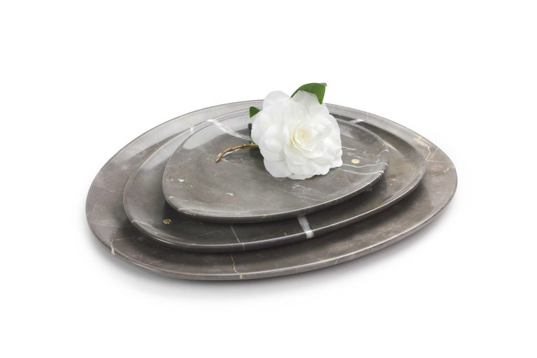 Hand carved presentation plates in Imperial Grey marble. Multiple use as plates, platters and placers. Dimensions: Small - L24 W20 H1.8 cm, Medium - L30 W28 H1.8 cm and Big - L36 W35 H1.8 cm.  Pieruga proudly creates elegant accessories and