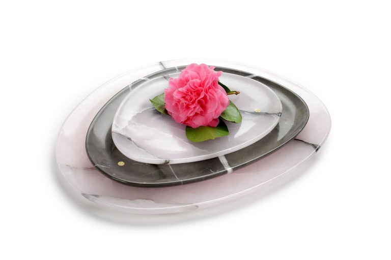 Hand carved presentation plates in pink onyx and imperial grey marble. Multiple use as plates, platters and placers. Dimensions: Small - L24 W20 H1.8 cm, Medium - L30 W28 H1.8 cm, Big - L36 W35 H1.8 cm.  Pieruga proudly creates elegant accessories