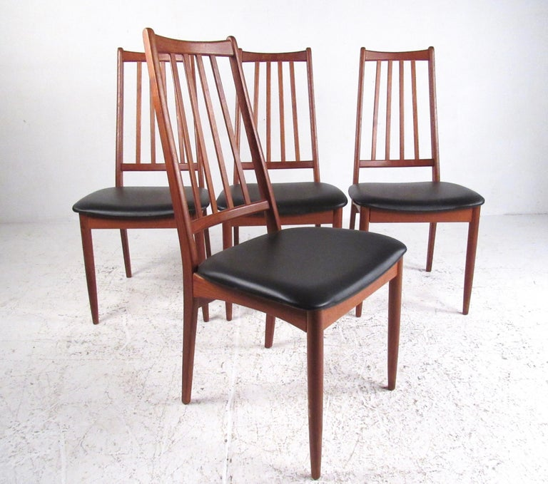 This stylish set of four Mid-Century Modern dining chairs features shapely spoked seat backs and with padded vinyl seats. Comfortable Scandinavian Modern design makes a striking addition to kitchen or dining room interiors. Please confirm item